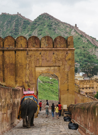 Jaipur, India - Jul 28, 2015. People with elephants going on the cobblestone path to Amber Fort in Jaipur, India. Elephant rides are popular tourist attraction in Amber Fort. Editorial