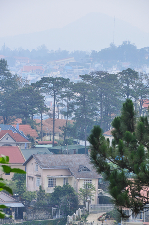 Dalat, Vietnam - Apr 7, 2013. Houses with pine trees at misty day in Dalat, Vietnam. Da Lat in Central Highlands, is centered around a lake and surrounded by hills, pine forests. Editorial