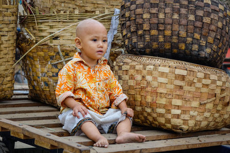 Yangon, Myanmar - Feb 25, 2016. A child sitting at local market in Yangon, Myanmar. Yangon is the country main centre for trade, industry and tourism.