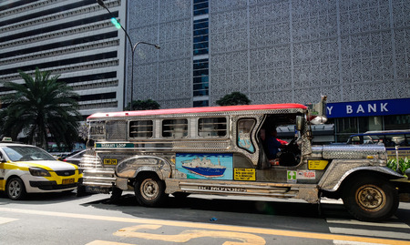 Manila, Philippines - Dec 21, 2015. A jeepney stopping on street at downtown in Manila, Philippines. Manila is a major center for commerce, banking and finance in Philippines.