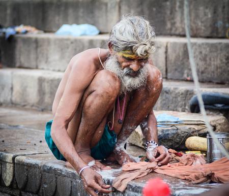 Varanasi, India - Jul 12, 2015. An old man washing clothes on the riverbank of Ganges in Varanasi, India. Varanasi draws Hindu pilgrims who bathe in the Ganges River sacred waters.
