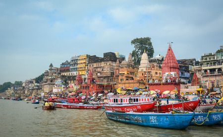 Varanasi, India - Jul 12, 2015. View of the riverbank of Ganges at sunny day in Varanasi, India. Varanasi draws Hindu pilgrims who bathe in the Ganges River sacred waters.