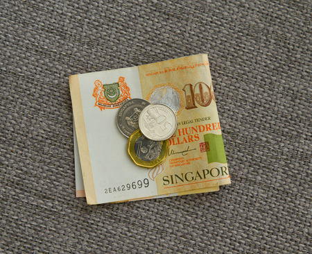 Singapore Dollar coins and banknotes on linen fabric. Close up. Money concept.