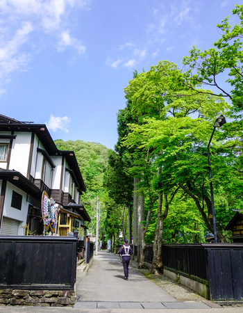 People walking on rural road at Kakunodate Samurai District in Akita, Japan. Kakunodate is a former castle town and samurai stronghold in Akita Prefecture.