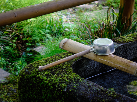 A Japanese ladle at Shinto temple in Akita, Japan. In Japan, a tsukubai is a washbasin provided at the entrance to holy places for visitors to purify themselves.