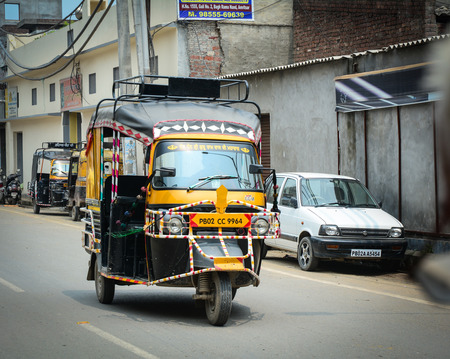Amritsar, India - Jul 25, 2015. A tuk tuk taxi running on street in Amritsar, India. Amritsar is a holy city in the state of Punjab in India. It lies about 25 km east of the border with Pakistan. Editorial