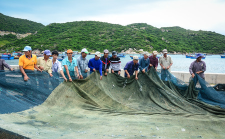 local 27: Phan Rang, Vietnam - Jan 27, 2016. Local men working with fishing nets in the village in Vinh Hy Bay, Phan Rang, Vietnam. Phan Rang is one of famous destinations in southern Vietnam. Editorial