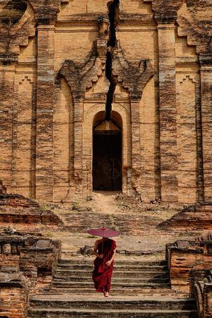 A Buddhist monk walking at Pahtodawgyi in Mandalay, Myanmar. Pahtodawgyi is an incomplete monument stupa in Mingun, approximately 10 km northwest of Mandalay. Stock Photo