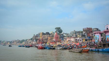 Varanasi, India - Jul 12, 2015. View of the riverbank of Ganges under blue sky in Varanasi, India. Varanasi draws Hindu pilgrims who bathe in the Ganges River sacred waters.