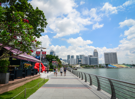 Singapore - Mar 13, 2016. Tourists walking at Marina Bay in Singapore. Singapore is one of the most popular travel destinations in the world for a lot of reasons.