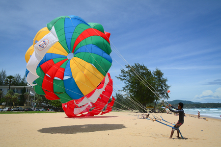 Phuket, Thailand - Jun 19, 2016. People playing parasailing at sunny day in Phuket, Thailand. Phuket is a heady mix of bustling bars, restaurants and truly spectacular dive locations.
