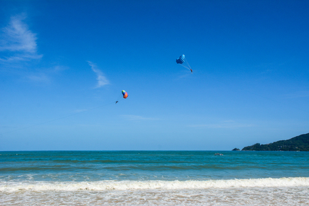 People playing parasailing on Patong beach in Phuket, Thailand. Phuket is a heady mix of bustling bars, night spots, restaurants and truly spectacular dive locations. Stock Photo