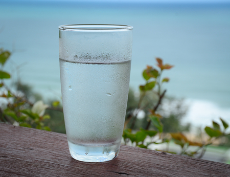 Glass of cold water on wooden table with seascape background. Close up.