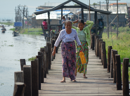lake district: Inle, Myanmar - Feb 14, 2016. People walking on wooden bridge in Inle Lake, Myanmar. Inle is a freshwater lake located in the Nyaungshwe of Taunggyi District of Shan State. Editorial