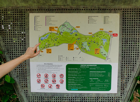 Singapore - Dec 14, 2015. A hand on the map of city park in Singapore. Singapore, referred to as the Lion City, the Garden City, is a sovereign city-state in Southeast Asia.