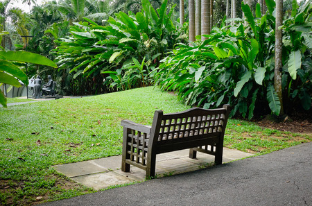 A wooden bench at botanic garden in Singapore. Singapore, referred to as the Lion City, the Garden City, is a sovereign city-state in Southeast Asia.