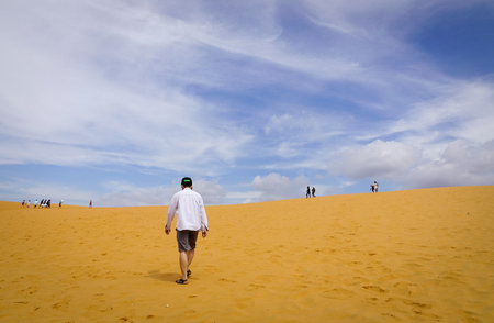 ne: A man walking on the sand dunes in Mui Ne, Vietnam. Sand Dunes just outside of Mui Ne are one of Vietnam charming geological oddities.