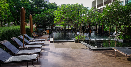Outdoor swimming pool at luxury hotel in Pattaya, Thailand. Pattaya is on the east coast of the Gulf of Thailand, about 100 km south-east of Bangkok.