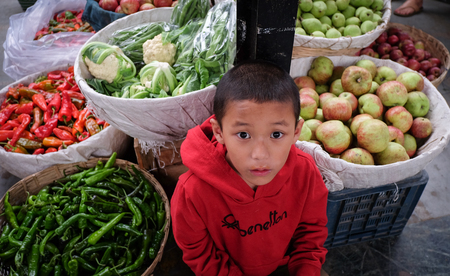 Thimphu, Bhutan - Aug 29, 2015. A boy at rural market in Thimphu, Bhutan. In South Asia, Bhutan ranks first in economic freedom, ease of doing business, and peace.