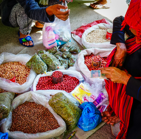 retailers: Yangon, Myanmar - Oct 17, 2015. Vendors selling nuts at the rural market in Yangon, Myanmar. Yangon is the country largest city with a population above seven million.