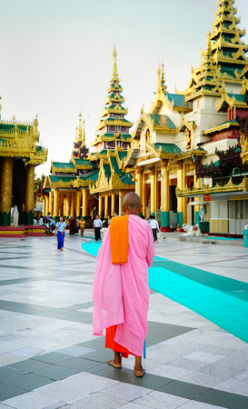Yangon, Myanmar - Oct 16, 2015. A nun walking at Shwedagon Pagoda in Yangon, Myanmar. Shwedagon (Great Dagon) Pagoda is the most sacred Buddhist pagoda in Myanmar.