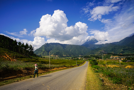 A woman walking on rural road in Sapa, Northern Vietnam. Sa Pa has the biggest market in the province and also is famous for the terraced rice fields.