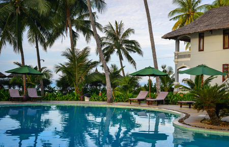 inground: Phan Thiet, Vietnam - Mar 26, 2017. Swimming pool of resrort with palm trees in Phan Thiet, Vietnam. Phan Thiet belongs to Binh Thuan province and located 200km South of Cam Ranh Bay. Editorial