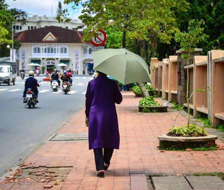 dalat: A woman with umbrella walking on street in Dalat, Vietnam. Da Lat is a popular tourist destination, located 1,500m above sea level on the Langbian Plateau. Stock Photo