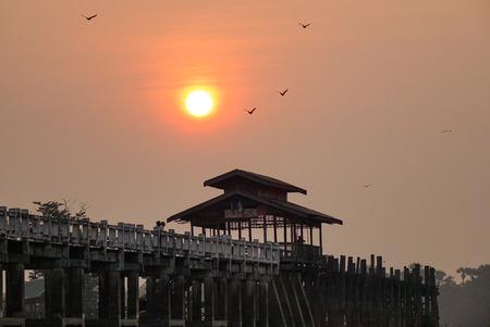 U Bein Bridge at sunrise in Mandalay, Myanmar. U Bein Bridge is the longest teakwood footbridge in the world, spanning 1.2km long. Stock Photo