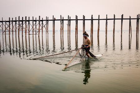 Mandalay, Myanmar - Feb 21, 2016. A man fishing near U Bein Bridge in Mandalay, Myanmar. U Bein Bridge is believed to be the oldest and longest teakwood bridge in the world.