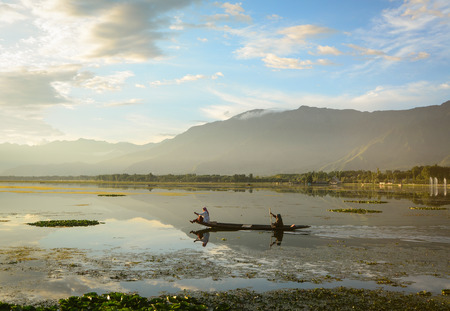 Srinagar, India - Jul 23, 2015. Women rowing boat on Dal Lake at sunset in Srinagar, India. Srinagar is the summer capital of the Indian state of Jammu and Kashmir.