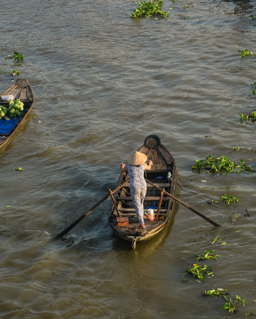 A woman rowing boat in Cai Rang, Vietnam. Floating market at Cai Rang is the old traditional market of South of Vietnam. Stock Photo