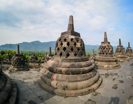 Borobudur Temple at sunny day on Java, Indonesia. Built in the 9th century, the temple was designed in Javanese Buddhist architecture.