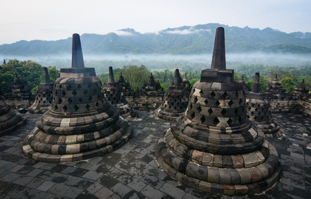 Stone stupas of Borobudur Temple at early morning on Java, Indonesia. Borobudur is one of world truly great ancient monuments, the single largest Buddhist structure.