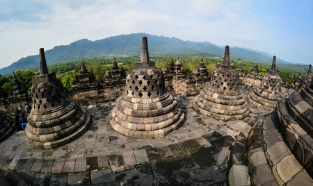 View of Borobudur Temple at sunny day on Java, Indonesia. Built in the 9th century, the temple was designed in Javanese Buddhist architecture. Stock Photo