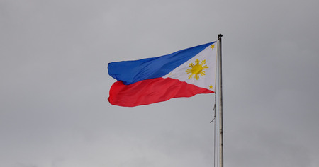 Philippines flag waving in the sky at downtown in Manila, Philippines.