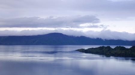 Lake Towada with mountains at sunset in Aomori, Japan. Lake Towada is the largest caldera lake on Honshu, Japan main island. Stock Photo