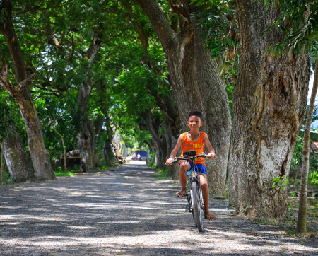 An Giang, Vietnam - Sep 1, 2017. A boy biking on rural road in An Giang, Vietnam. An Giang lies in the Mekong Delta and tributaries of the vast Mekong River run through its fertile landscape.
