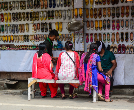 Amritsar, India - Jul 25, 2015. People at shoes shop in Amritsar, India. Amritsar is home to the Harmandir Sahib, the spiritual and cultural centre for the Sikh religion.