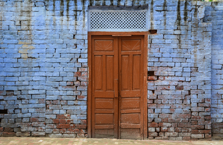 Old brick wall with wooden door at ancient town in Amritsar, India. Amritsar is a holy city in the state of Punjab in India. Stock Photo