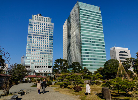 Tokyo, Japan - Jan 3, 2016. Modern buildings with green park at downtown in Tokyo, Japan. The Tokyo urban area 38 million people had a total GDP of 2 trillion USD in 2012.