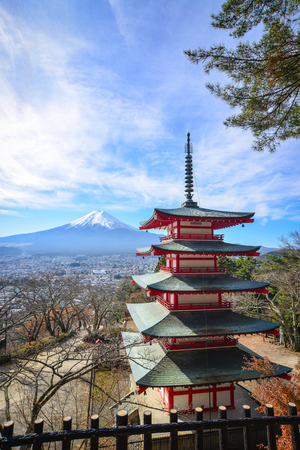 View of Chureito Pagoda with Mount Fuji in Yamanashi, Japan. The pagoda is a five storied pagoda resting on the side of a nearby mountain facing Fuji.
