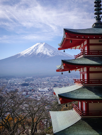View of Mount Fuji from Chureito Pagoda at sunny day. Chureito Pagoda is surrounded by cherry trees and overlooking Mt. Fuji.