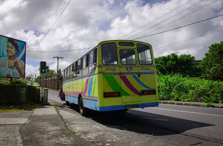 Port Louis, Mauritius - Jan 6, 2017. A bus running on rural road at sunny day in Port Louis, capital of Mauritius. Port Louis is the business and administrative capital of the island. Editorial