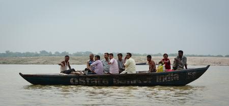 benares: Varanasi, India - Jul 12, 2015. Tourist boat on the Ganges River at rainy day in Varanasi, India. Varanasi, also known as Kashi and Benaras, is the cultural capital of India.