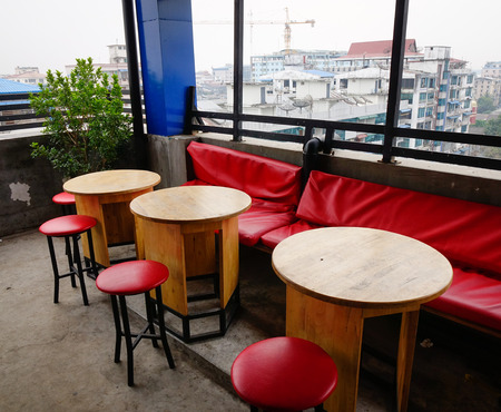 Chairs and tables at coffee shop with city view in Yangon, Myanmar.