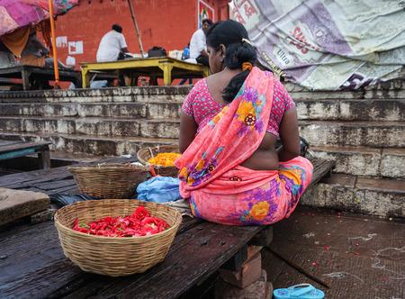 benares: Varanasi, India - Jul 11, 2015. Indian woman sitting on Ganges riverbank at sunrise in Varanasi, India. Varanasi draws Hindu pilgrims who bathe in the Ganges River sacred waters.