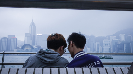 Hong Kong - Mar 29, 2017. An Asian gay couple on embankment of Victoria Harbor in Hong Kong. In 2014 Hong Kong was the 11st most popular destination for international tourists.