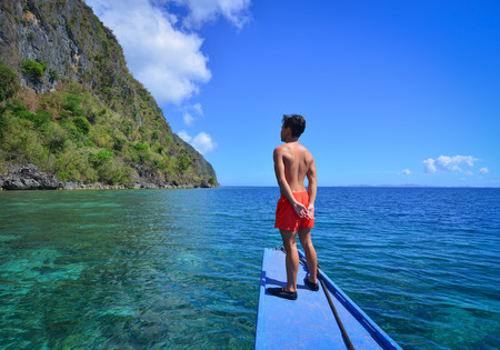 A man standing on wooden boat in Coron Island, Philippines. Coron is known for several Japanese shipwrecks of World War II vintage.