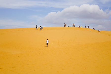 ne: People playing on sand dunes at summer day in Mui Ne, Vietnam. Mui Ne is a coastal fishing town in the Binh Thuan Province of Vietnam. Stock Photo